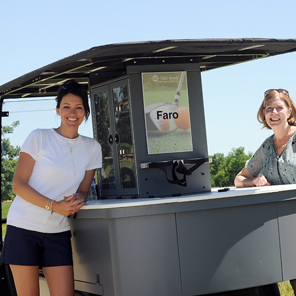 Image of Shannon Sharrock from Faro International and our Project Manager Sybil Weiss operating a beverage cart for the 2016 Golf Tournament