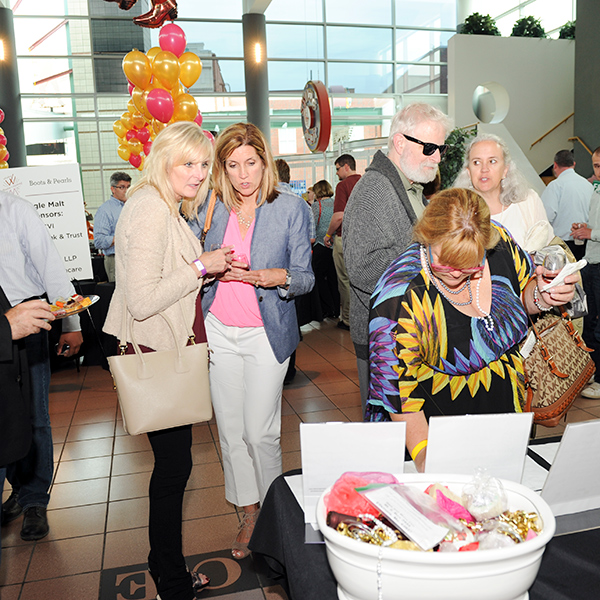 Image of guests at the 2015 Boots & Pearls Event admiring auction items