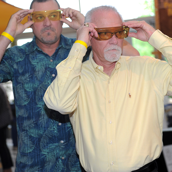 Images of two guests at Boots & Pearls participating in the Low Vision Experience
