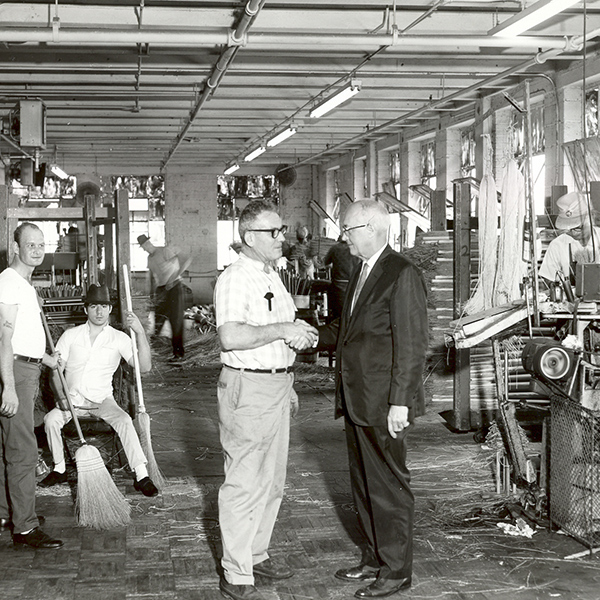 Black and white image of our former broom workshop in the 60's. Our foreman shaking hands with a gentleman in a suit in the center.
