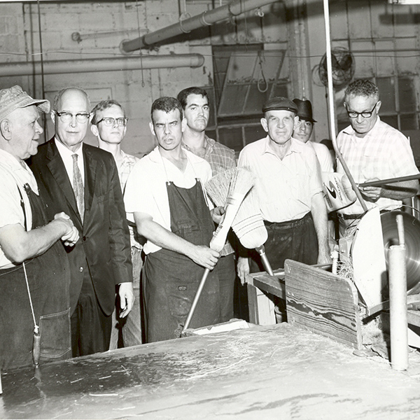 Black and white image of a few male employees in our former broom workshop