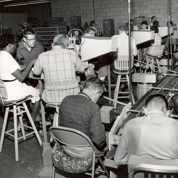 Black and white image of employees assembling pens in our former workshop