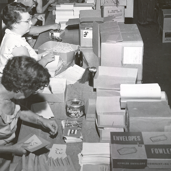 Black and white image of female employees making envelopes in our former workshop