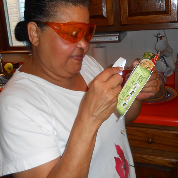 Image of Angela using a magnifier to read microwave instructions for a frozen meal