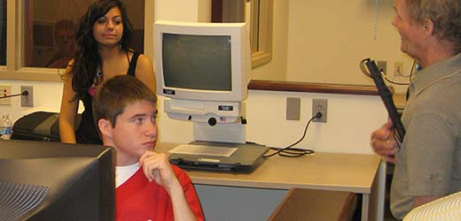 Image of student in our computer lab with technology instructor, Jim Fettgather