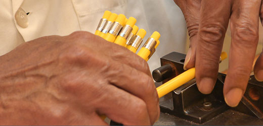 Image of hands assembling yellow wax pencils