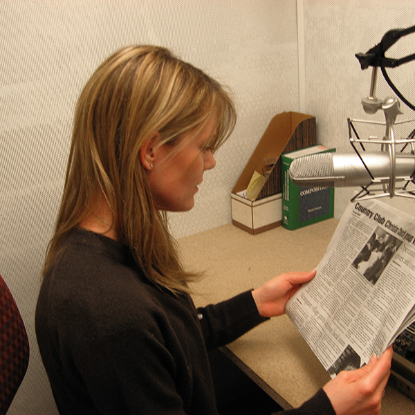 Image of an audio reader volunteer reading a newspaper in the recording booth