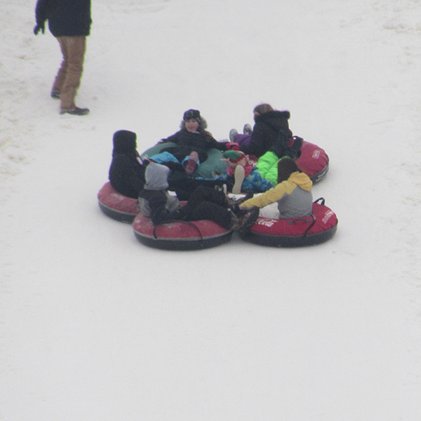 Image of a group of our youth on a tube during a Totally Tubing event