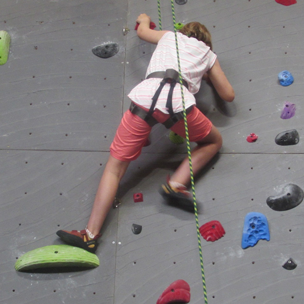Image of a young girl in our youth program rock climbing