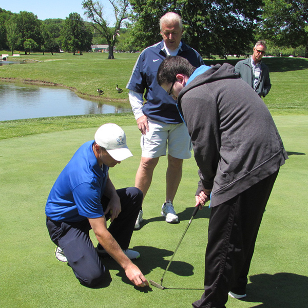 Image of one of our EYE participants learning techniques from a golf pro at the Golf Clinic