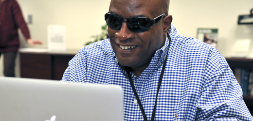Image of male client using a computer smiling