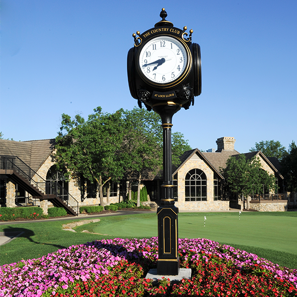 Image of a clock post in a bed of red and pink flowers on the green at the Country Club at Loch Lloyd