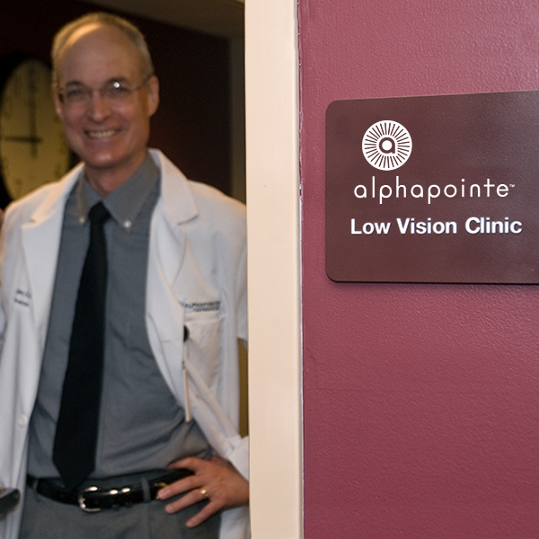 Image of Dr. Metzger opening the door to the exam room of the low vision clinic with a smile on his face