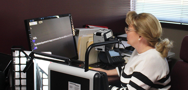 Image of our Intake Coordinator Cheryl Rayburn using ZoomText at her desk