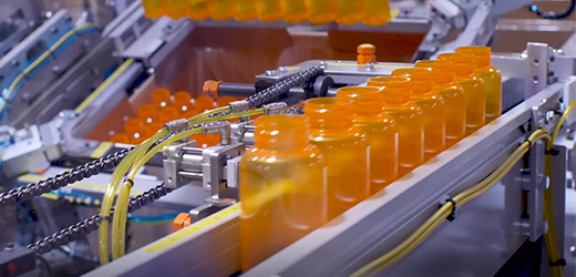 Image of our plastic medicine bottles coming through on the conveyor belt fresh out of the machine