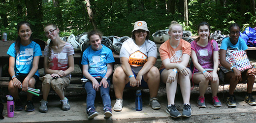 Group photo of Adventure Campers in the woods on a bench smiling, waiting for there chance on the rock wall