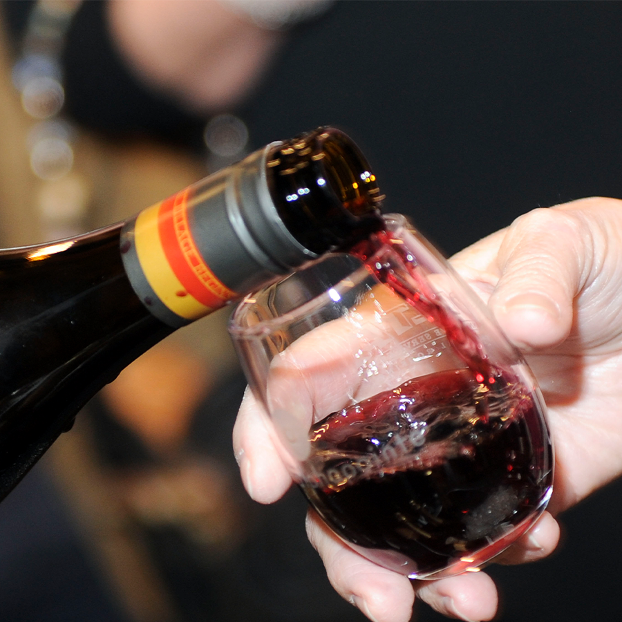 An extreme close up of red wine being poured into a tasting glass