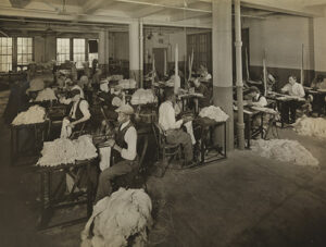 Workers with vision loss stitching mops (1930). Image credits: Byron Company (New York, N.Y.). Museum of the City of New York.
