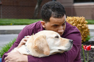 Image of Alphapointe team member Devin Williams with his guide dog, Ace