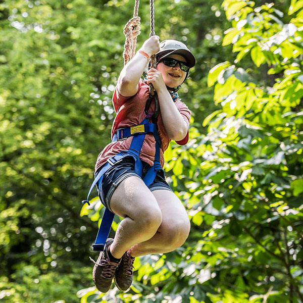 Adventure camp participant Lyra going down the zip line